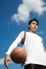 An asian basketball player holding a basketball outdoor