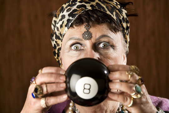 Gypsy looking at an eight ball to predict the future
