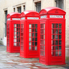 A photography of three old red phone boxes in London