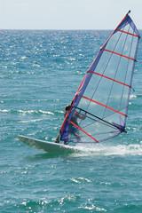 Windsurfer racing at speed on beautiful turquoise choppy sea
