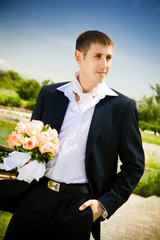well-dressed groom with rose bouquet