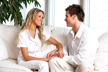 Young love couple smiling in the comfortable apartment.