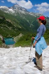 Hiker girl looking to mountain lake