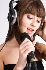 Woman in headphones Singing in to Microphone