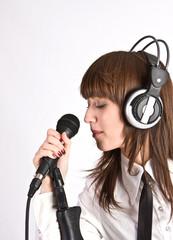 Woman in headphones Singing in Microphone