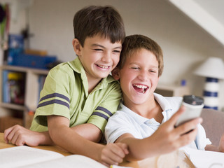 Two Young Boys Distracted From Homework, Playing With Cellphone