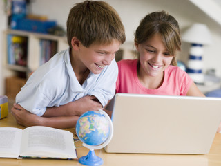 Boy And Girl Doing Their Homework On A Laptop
