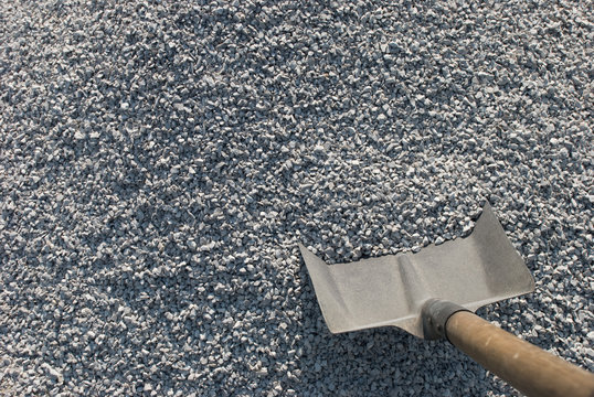 A Shovel stick out of the pile of gravel.
