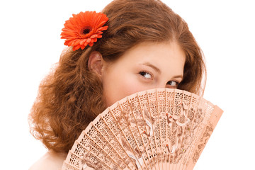 Young beautiful woman face behind Chinese fan