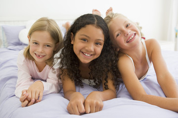 Three Young Girls Lying On A Bed In Their Pajamas