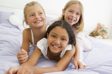 Three Young Girls Lying On Top Of Each Other In Their Pajamas