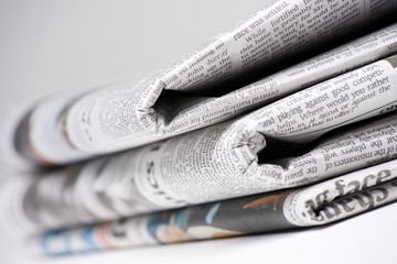Newspapers on light background with shallow depth of focus