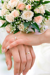 hands of new married with golden rings and bouquet
