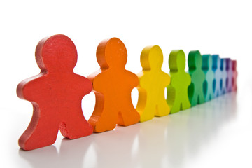 Brightly colored wooden people isolated on a white background.