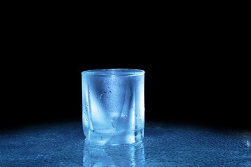 Glass of cold water standing on dark background