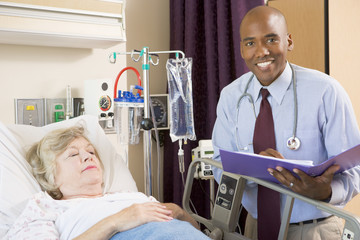 Doctor Making Notes About Senior Woman Lying In Hospital Bed