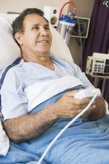 Middle Aged Man Pressing The Call Button In Hospital