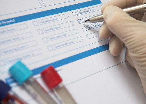 Doctor ticking box on a blood test form