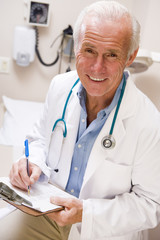 Middle Aged Doctor Writing On His Clipboard