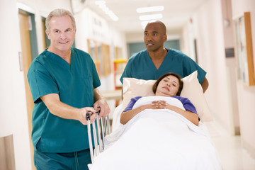 Two Orderlies Pushing A Woman In A Bed Down A Hospital Corridor
