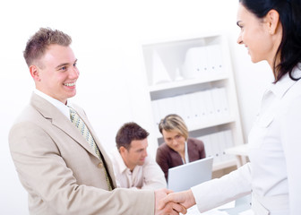 Businessman and businesswoman shaking hands in office,