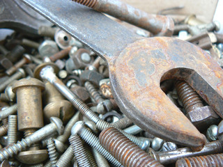 Assortment of rusty metal fasteners and wrench