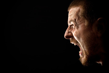 Face of angry man screaming isolated on black