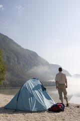Mann steht neben seinem Zelt an einem Bergsee