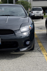 Black automobile's driver's front bumper and headlight