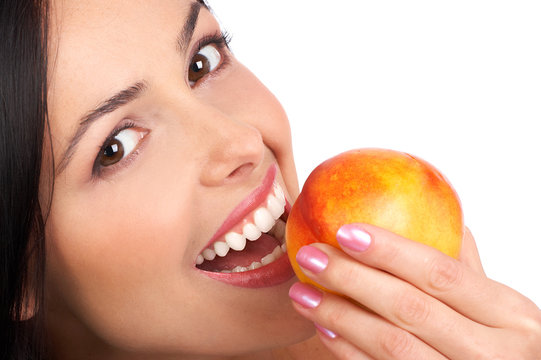 Beautiful young woman eating a peach. Isolated over white.
