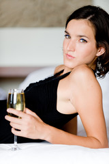 A young woman drinking champagne on the bed