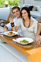Young couple on vacation eating lunch at a outdoor restaurant