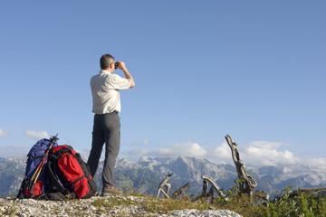 Wanderer mit Rucksack schaut mit Fernglas in die Landschaft