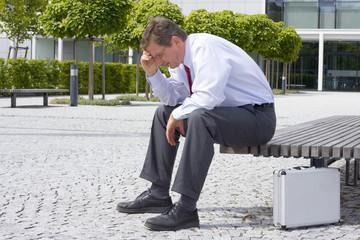 Müder Manager sitzt auf Bank vor Bürogebäude