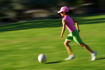 Young girl running with a ball