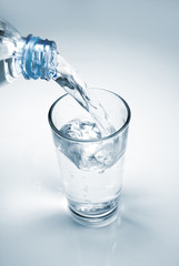 Glass of water being filled from a plastic bottle