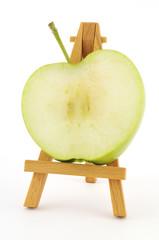 Green apple slice on wooden easel