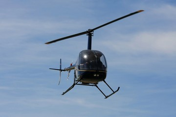 Modern helicopter flying in the blue sky
