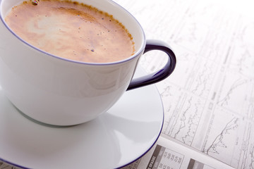 Cup coffee on a morning business newspaper