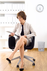 Portrait of a senior businesswoman sitting in office chair.