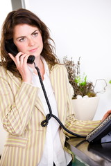 Young female receptionist receiving phone calls