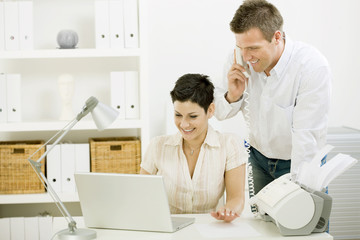 Happy couple working at home using laptop computer