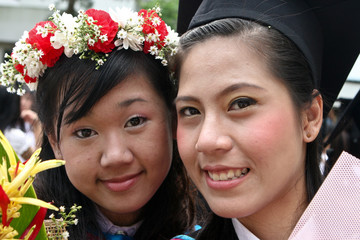 Beautiful Asian university graduates celebrate their success.