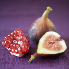 still life of a part of pomgranate, whole and a slice of fig