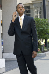 African-American model walking and talking on a cell phone
