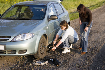 man helping for woman to change broken wheel