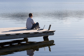 man sitting on pier above lake water with laptop