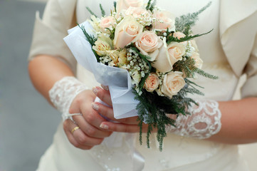 Brides's hands in lacy signet with wedding bouquet