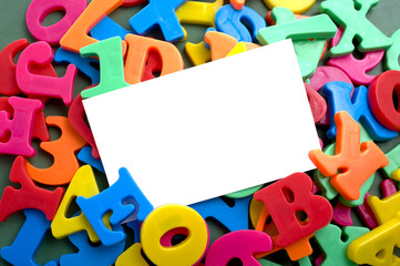 A white notecard surrounded by brightly colored plastic letters