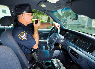Police officer in his squad car, talking on his radio.